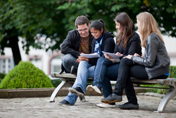 Students sitting on a bench outside at the Gengenbach campus
